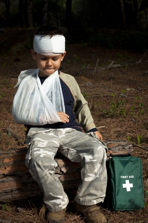 First Aid treatment given to a young boy in the forest, showing an arm sling and a head injury.