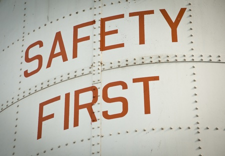 A Metal work sign painted with the words SAFETY FIRST.