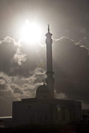 A mosque in Gibraltar with the sun breaking through the clouds.