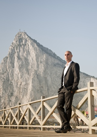 A business man looking out to sea standing in front of the rock of Gibraltar. Stock Photo