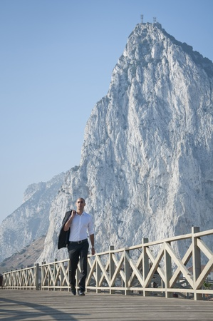 A business man looking walking along the beach front in front of the rock of Gibraltar. photo