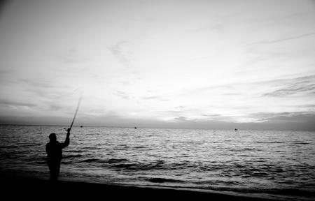 Der frühe Vogel fängt den Wurm, wie sie sagen, und hier hat man einen Fischer Gießen seine Linie bis in den Morgen Sonnenaufgang. Standard-Bild