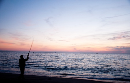 The early bird catches the worm as they say, and here you have a fisherman casting his line into the morning sunrise. photo