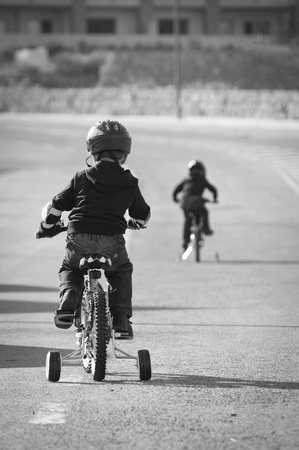 Two young children learning to ride their bikes, photographed in black & white.