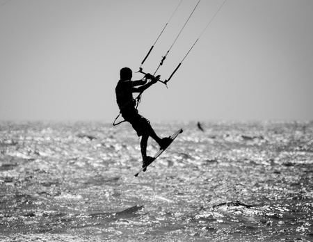 A Silhouette of a kite surfer in a Black   White finish