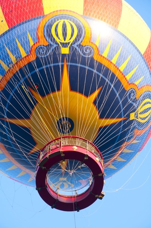 A hot air balloon coming down to ground with very nice colours  photo