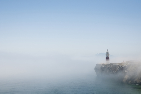 europa: Gibraltars lighthouse at Europa Point standing in the mist with Africa in the distance.