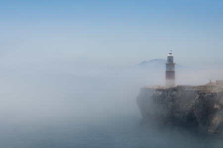 gibraltar: Gibraltars lighthouse at Europa Point standing in the mist with Africa in the distance.