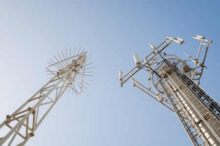 Two communication antenna towers equipped with a range of cell units.
