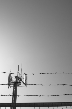 A communication antenna towers above equipped with a range of cell units protected behind a barbed wire fence. Stock Photo - 14018233