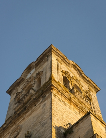 symetry: A church tower in the town of Arcos de la Frontera shining in the evening sunlight. Stock Photo