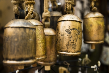 cloche: An old antique collection of hanging goldedn Cow Bells.