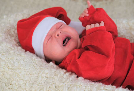 baby in santa costume on white background.Christmas toddler in Santa hat.Baby in red costume and hat.