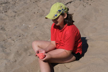 The girl has red slime in her hands. The girl is always enthusiastic about playing with slime, even on the beach playing with slime calms her down.