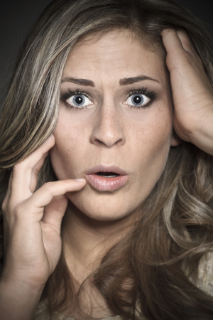 disbelief: Young blond woman looks frightened with hands on face