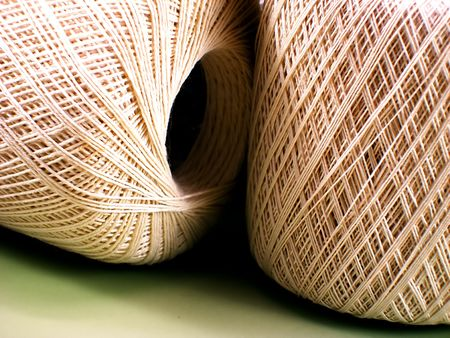 Two skeins of ecru bedspread-weight crochet thread.