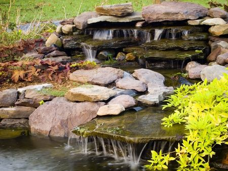 Water feature with rocks, ornamental plants, and flowing waterfalls. Stock Photo