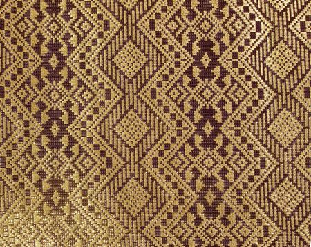 Detail of rich gold and deep purple fabric with an Oriental diamond pattern woven with gold thread.