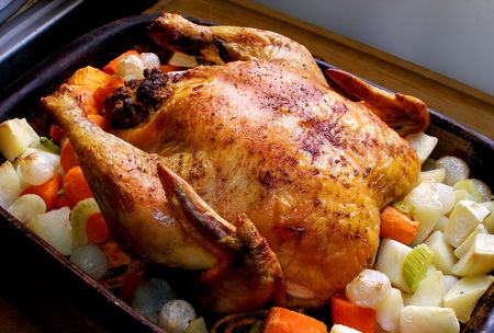 satisfying: Whole roasted chicken with vegetables in the roasting pan. Stock Photo