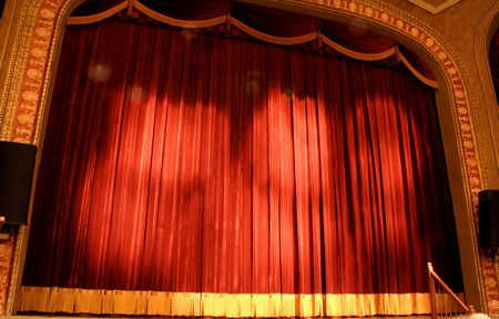 Crimson velvet stage curtain at a newly renovated Schwartz Center for the Arts in Dover, Delaware. Lens flares from the theatre lights emphasize the drama of the stage. Stok Fotoğraf