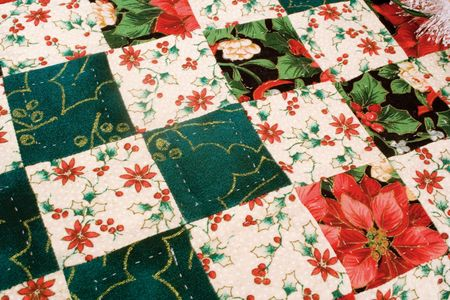 Hand crafted homemade quilt of red and green with very fine quilting stitches displayed on a table.