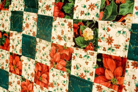 Hand crafted homemade quilt of red and green with very fine quilting stitches displayed on a wall.
