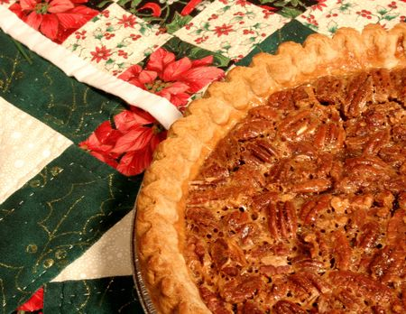 Pecan pie with a golden brown crust on a Christmas quilt background. Stok Fotoğraf