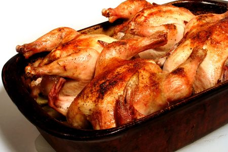 Four golden brown cornish game hens in a stone baking dish on a white background. Stock Photo