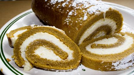 Pumpkin roll dessert with cream cheese filling on a white plate with green lines.