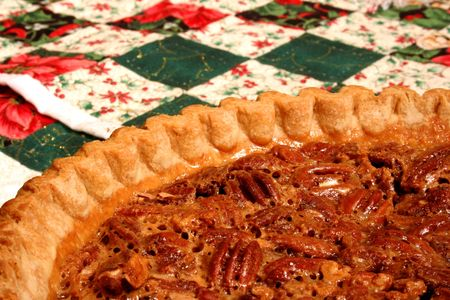 Pecan pie with a golden brown crust on a Christmas quilt background. Stock Photo