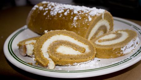 satisfying: Partially sliced pumpkin roll with cream cheese filling powdered sugar on top.