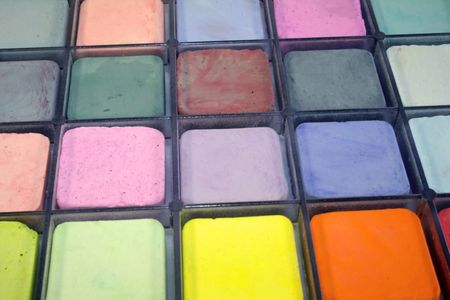Photograph of an assortment of pastel chalks in a black tray.