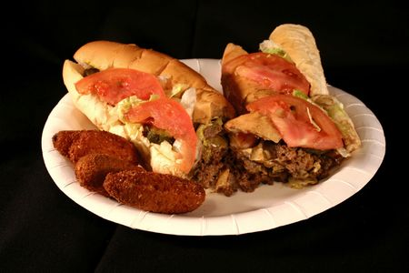 poppers: Cheese steak sandwich on a white paper plate with deep fried jalapeno poppers on a black velvet background.