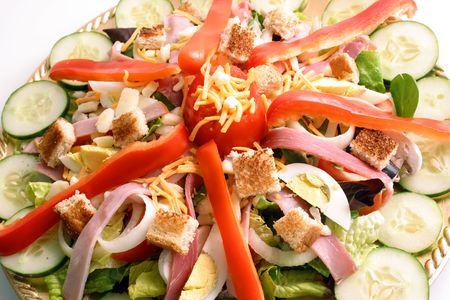 Close up view of a Chefs Salad artfully arranged on a gold-tone platter.