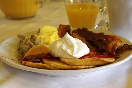 Restaurant breakfast of pancakes, eggs, bacon, potatoes, and orange juice. Stock Photo - 790274