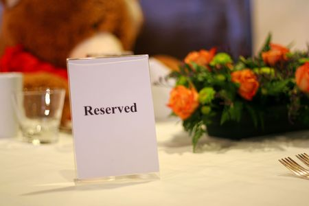 Reserved table at a fancy restaurant with at large teddy bear and roses. Stock Photo - 790283