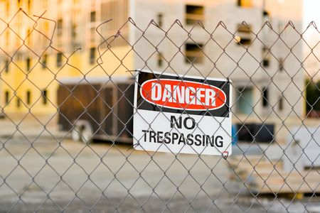 Warning Sign on a Fence Around a Construction Site