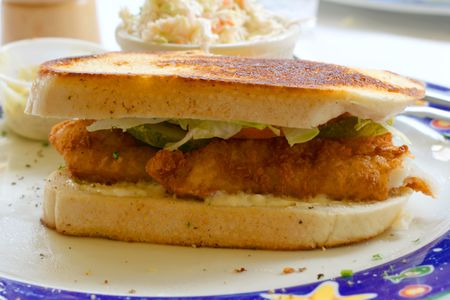 satisfying: Fried flounder sandwich with side dishes at a seafood restaurant. Stock Photo
