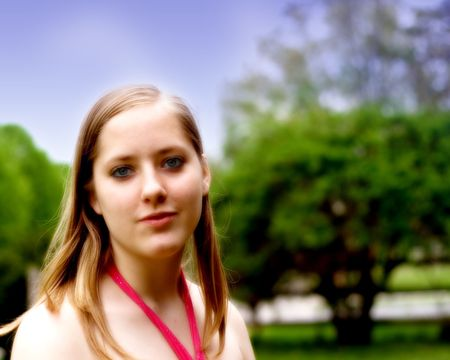 Smiling teen girl outdoors wearing a pink prom gown. photo