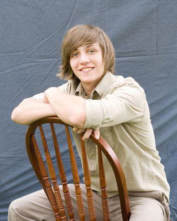 teenaged boy: Outdoor spring portrait of a teenaged boy sitting in a chair.