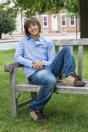 teenaged boy: Outdoor spring portrait of a teenaged boy and a bench. Stock Photo
