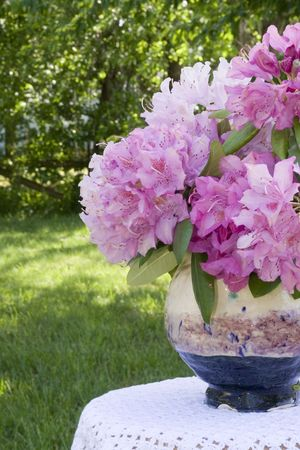 Pink Rhododendrons in a handcrafted vase on a small table covered with a crocheted tablecloth. Stock Photo - 948743