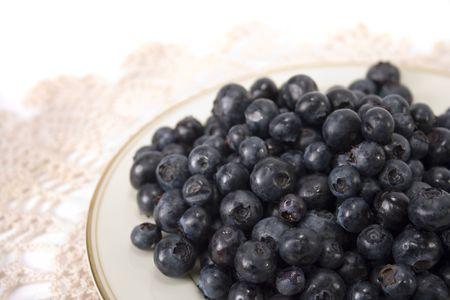 ecru: Blueberries on a gold trimmed plate on an ecru doily