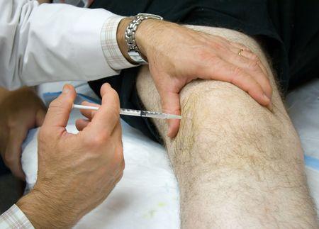 de rodillas: M�dico que den la inyecci�n en la rodilla de un paciente