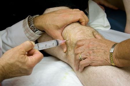 treatment: Doctor Giving Injection in the Knee of a Patient