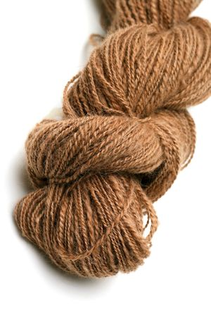 Skein or hank of natural fawn colored hand spun alpaca yarn on a white background photo