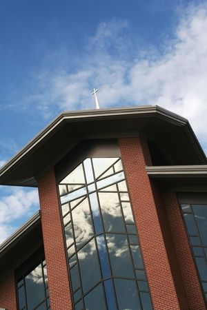 View from the Ground of a Cross Atop a Church with Clouds Reflecting on the Glass Windows