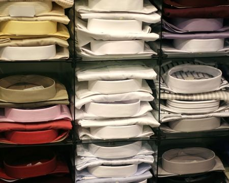 Dress Shirts Stacked on Shelves in a Mens Wear Store