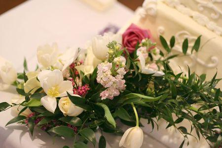 Wedding Bouquet on the Table next to the Wedding Cake Stock Photo