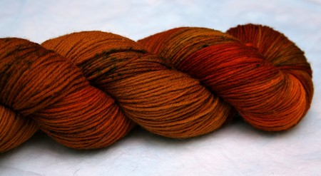 Close up view of details of rusty red hand dyed yarn for knitting, crocheting or weaving.